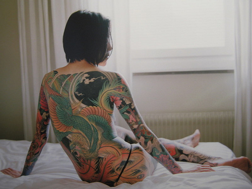 Woman sitting on a bed naked with her back covered in tattooes.