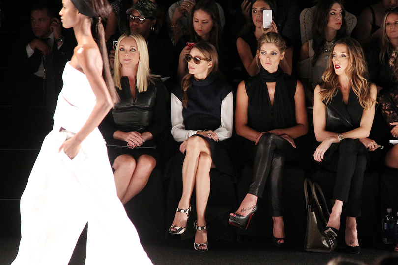 "Model on the fashion runway observed by front row fashionistas and bloggers sitting in ""the frow""."