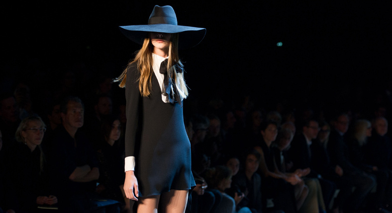 Model in a black dress and black hat walking the runway in front of an audience