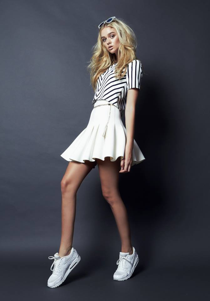 Model standing in white flared skater skirt and short sleeved black and white top with blonde hair in photo shoot