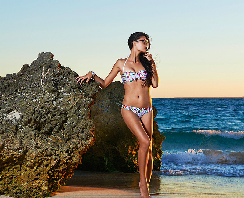 Model on the beach wearing floral two piece bikini at sunset