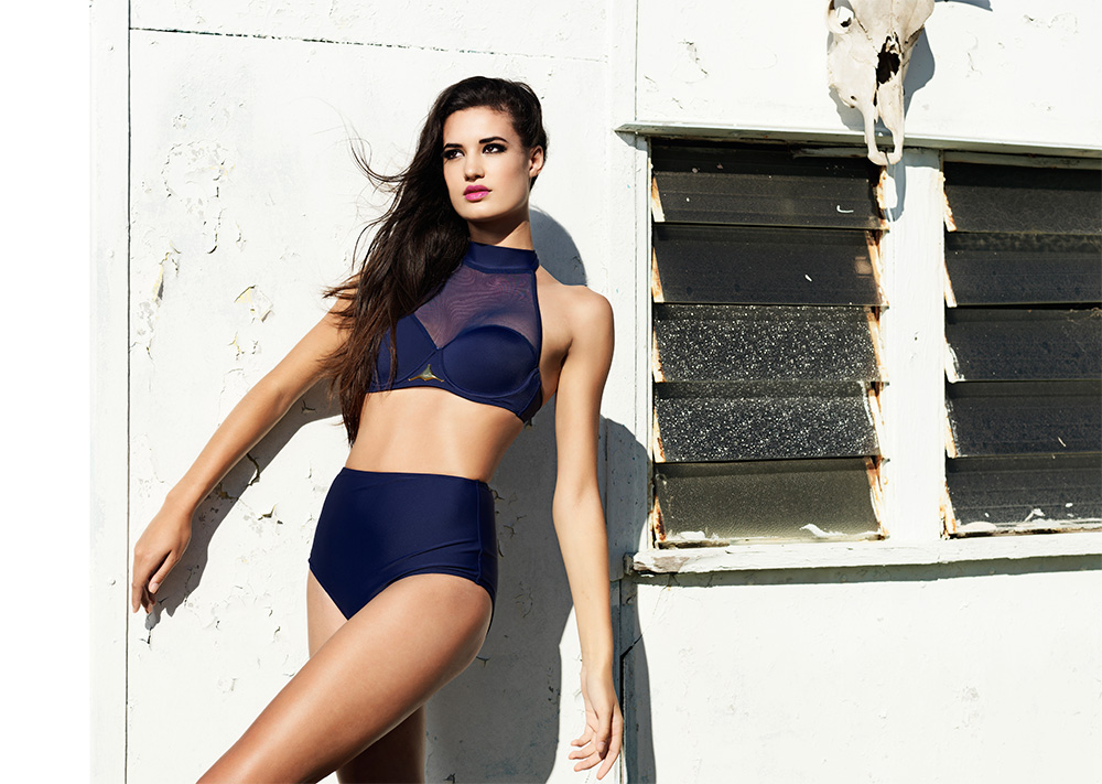 Girl standing modelling a two piece navy swimsuit and standing against the white wall of a building