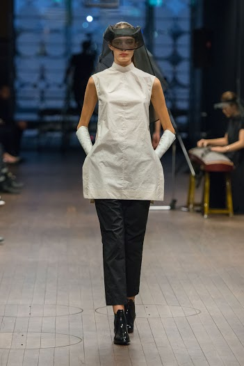 Model walking down the catwalk at the Lui Hon Runway show in Melbourne in white dress/top and black pants