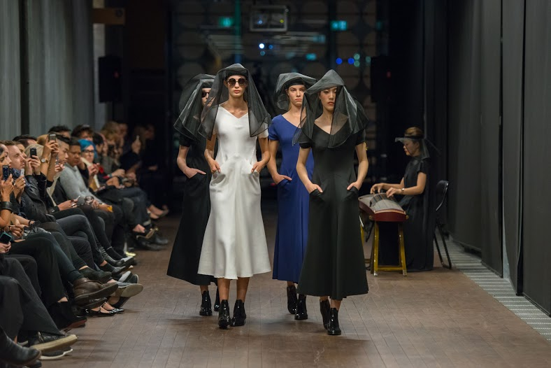 Four models walking down the catwalk at the Lui Hon runway show in Melbourne in different coloured dresses.