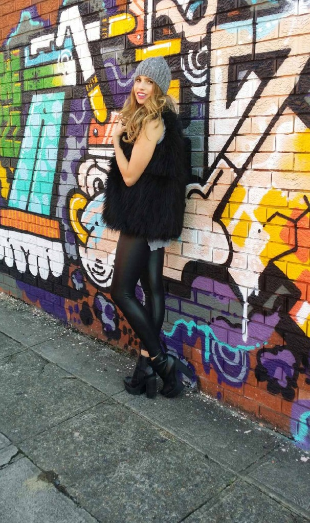 Emelia Roberts standing next to a graffiti wall of colour in an urban street on a modelling shoot