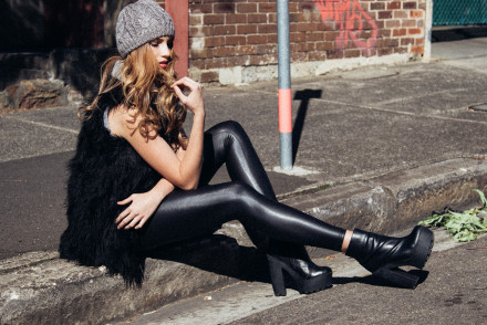 Emelia Roberts urban photo shoot sitting on the curb in a suburban street in wet look pants and beenie