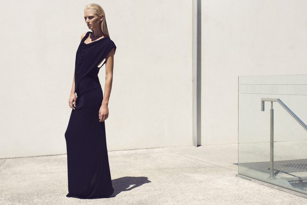 Photograph of a model with blonde hair standing in the full sunlight against a white wall in a black maxi dress