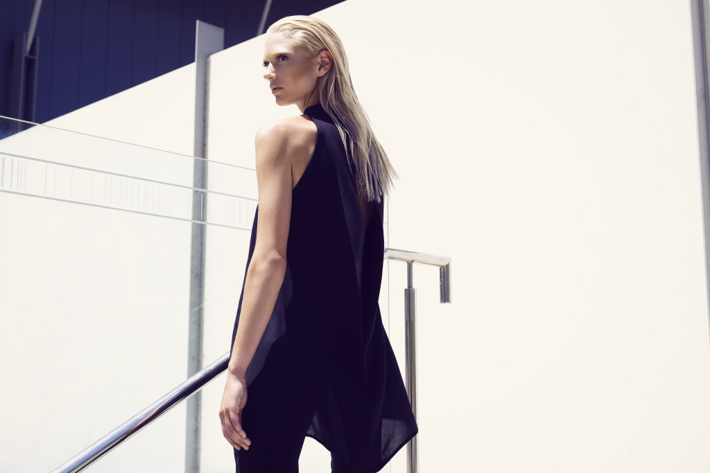Model standing in the full sunlight against a white wall in all black