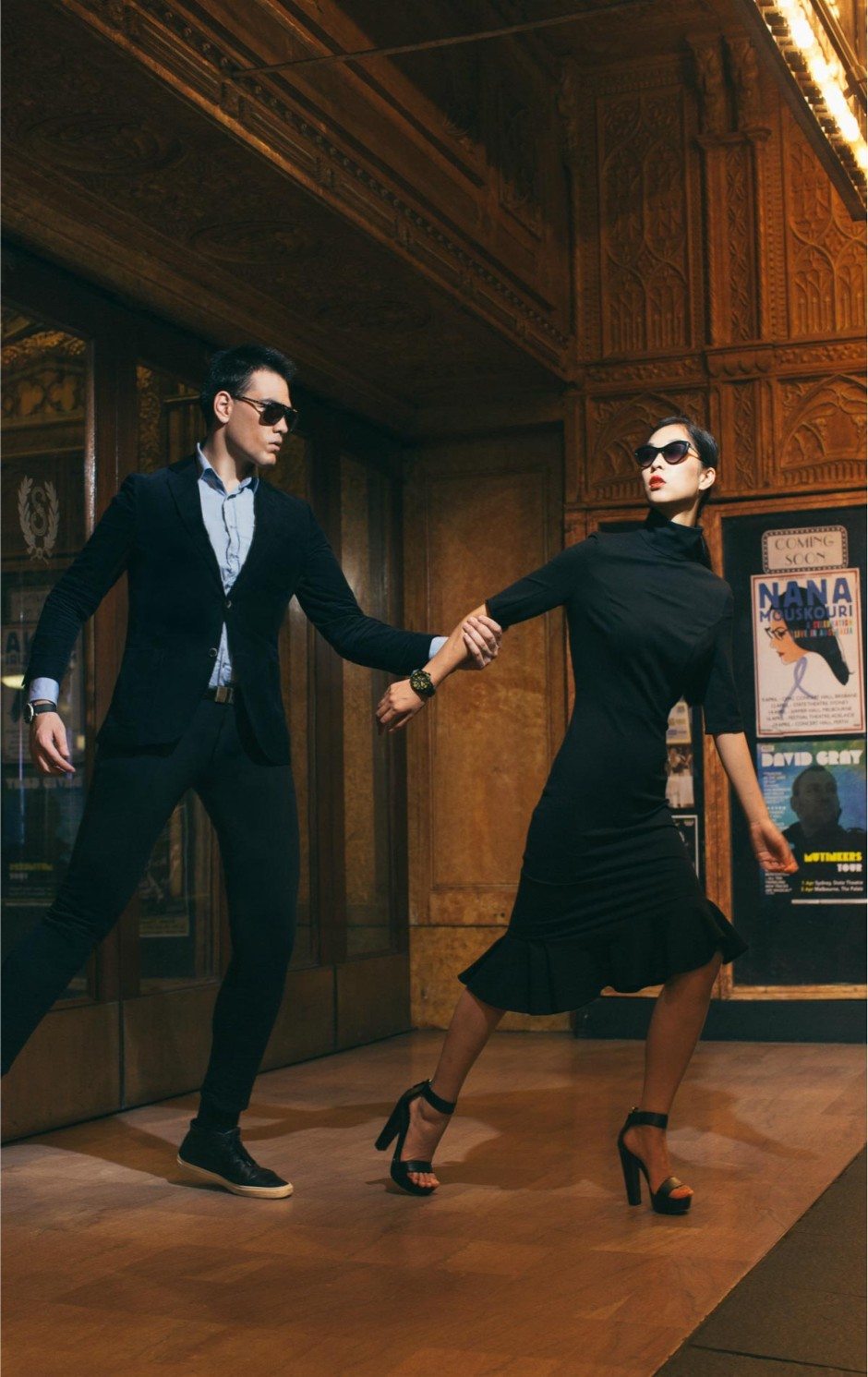 A male and female model walking through the State theatre in elegant clothing