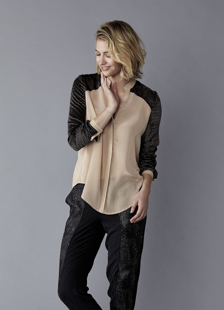 Model in a studio wearing apricot and black blouse with black pant