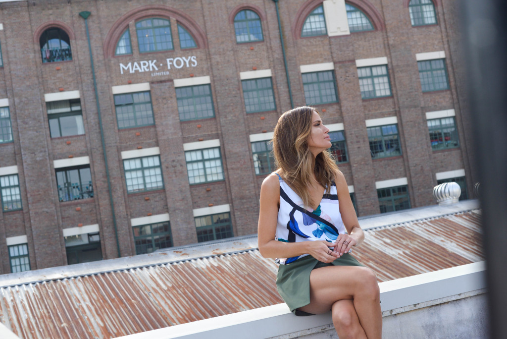 Jodi Gordon sitting in a modelling shoot for Seduce on the top of a building with a city scape behind.