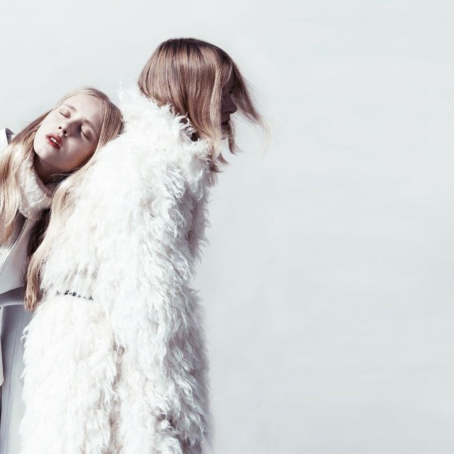 Two girls modelling Seduce clothing in a studio shot, one girl standing in a white fluffy coat.