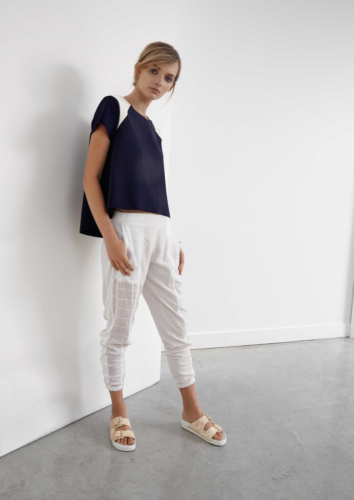 Girl standing in an empty room with concrete floor wearing white pant and black top in modelling shoot