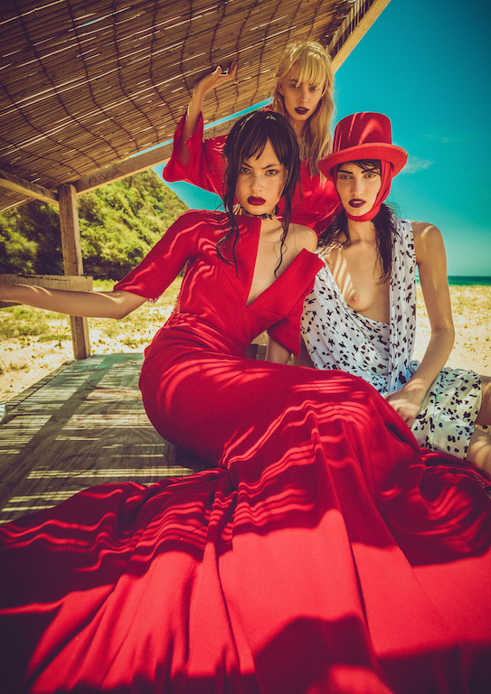 Three models on a beach under a hut dressed in red predominantly with clear blue sky behind