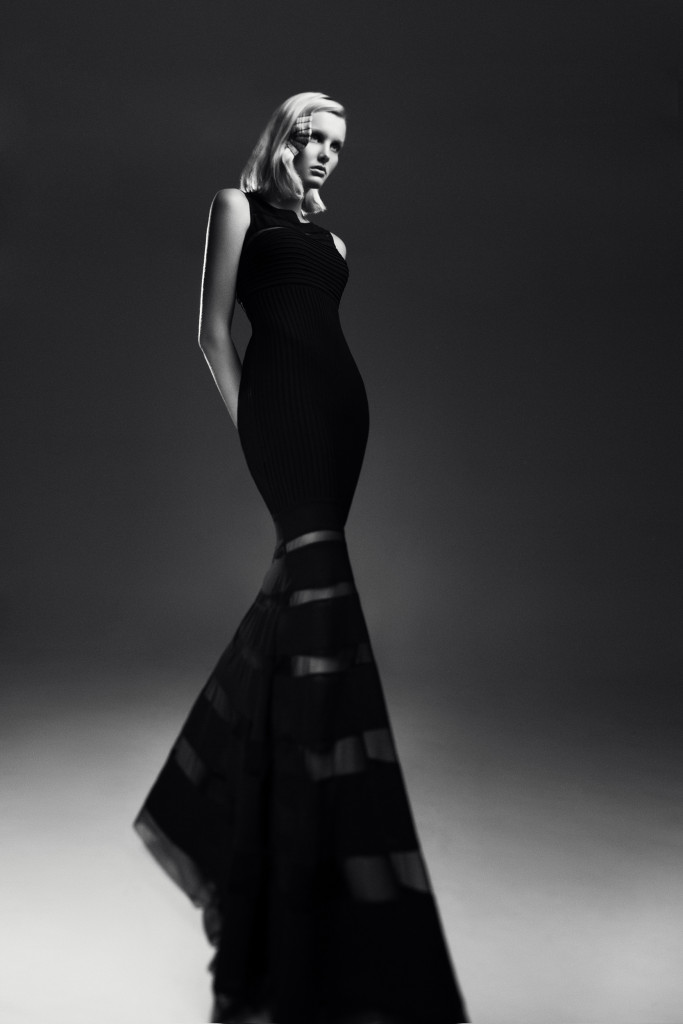 Model standing in a studio photographic shoot wearing a black dress with a fishtail.