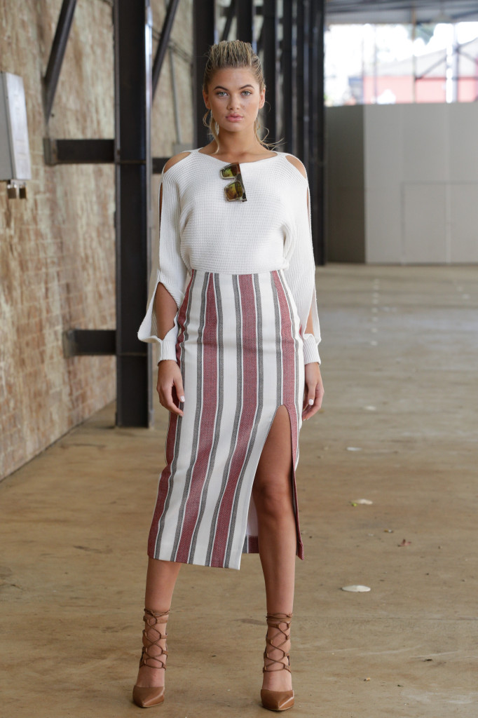 Model standing in a white blouse tucked into a striped white and brick red pencil skirt.