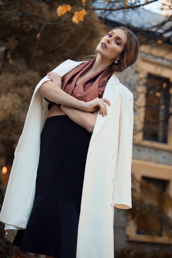 Model standing outside with arms crossed and a white jacket around her shoulders.j