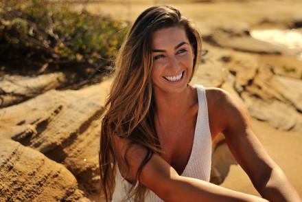 Rebecca Colalillo modelling on seaside rocks for her new tanning product GlowbyBeca.