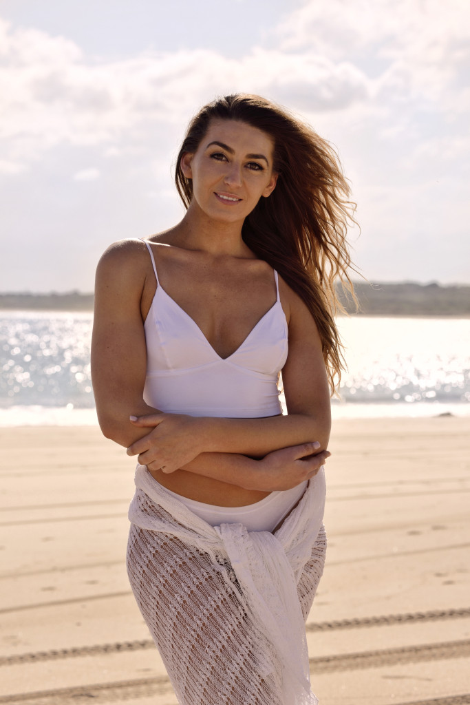 Rebecca dressed in bikini and wrap modelling on an Australian beach.