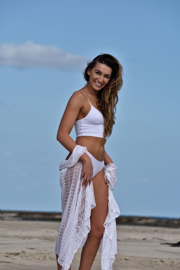 Rebecca Colalillo modelling on seaside rocks for her new tanning product GlowbyBeca.