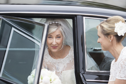 Bride stepping out of the vintage Daimler at the church.