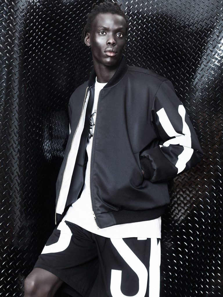 Autumn/Winter 2015 Male model standing in front of a black and white wall in a black bomber jacket and street wear pants.
