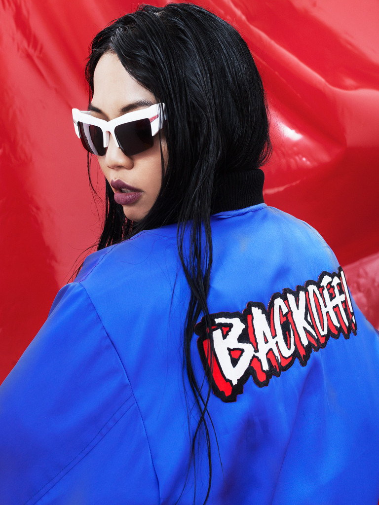 Autumn/Winter 2015. Asian model sitting in front a red vinyl sheet in a blue bomber jacket with writing across the back of the jacket. The model is being photographed in white mirrored sunglasses.