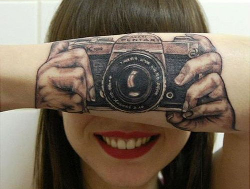Girl smiling looking at the camera with her arm folded in front of her face with a tattoo on her arm of two hands holding a picture. So it looks like she is taking a picture of her arm.