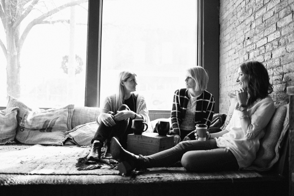 Michelle Houghton and her Instagram friends sitting around talking in a large room with a big open window on a cloudy day.