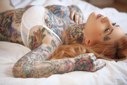 Girl lying on a bed wearing a bra but covered in tattoos.