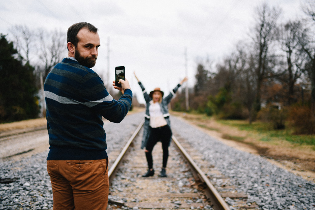 Jenn Fortner and Zac Fortner standing on train tracks for an Instagram pic
