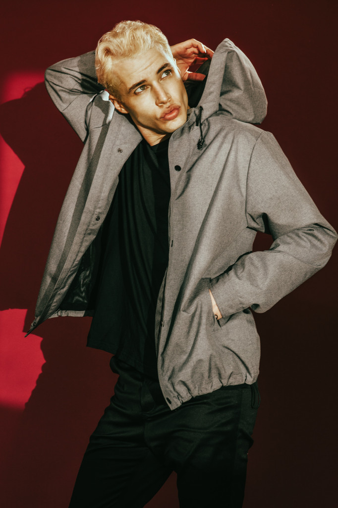 Model standing in front of a red wall dressed completely in black but wearing a donkey brown jacket with hoodie.