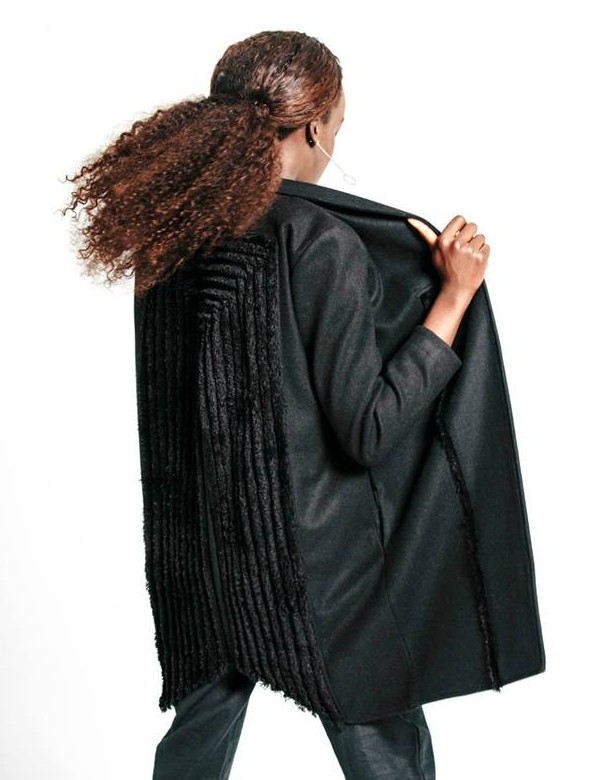 Studio shot of the back view of model Dijok Mai standing in a black Lois Hazel jacket.