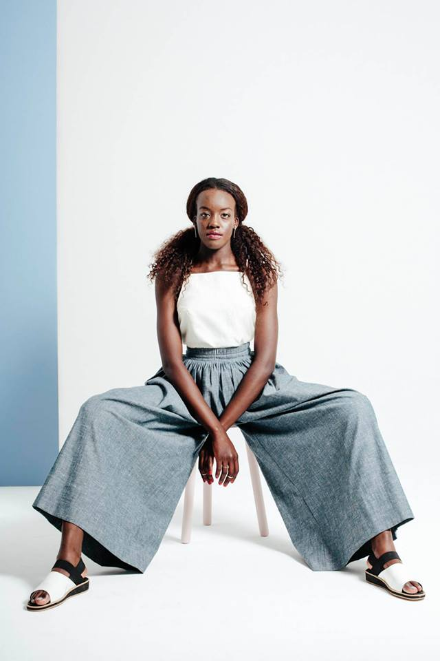 Studio shot of model Dijok Mai sitting on a white stool modelling Lois Hazel, wearing blue wide pant and white top with shoe string straps, flat white sandals with black elastic detail.