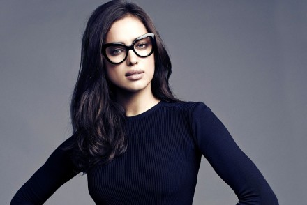 Model Irina Shayk in black dress and glasses with long dark hair.