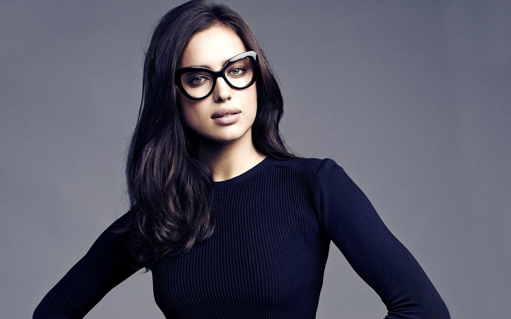 ba9091219 Model Irina Shayk in black dress and glasses with long dark hair.