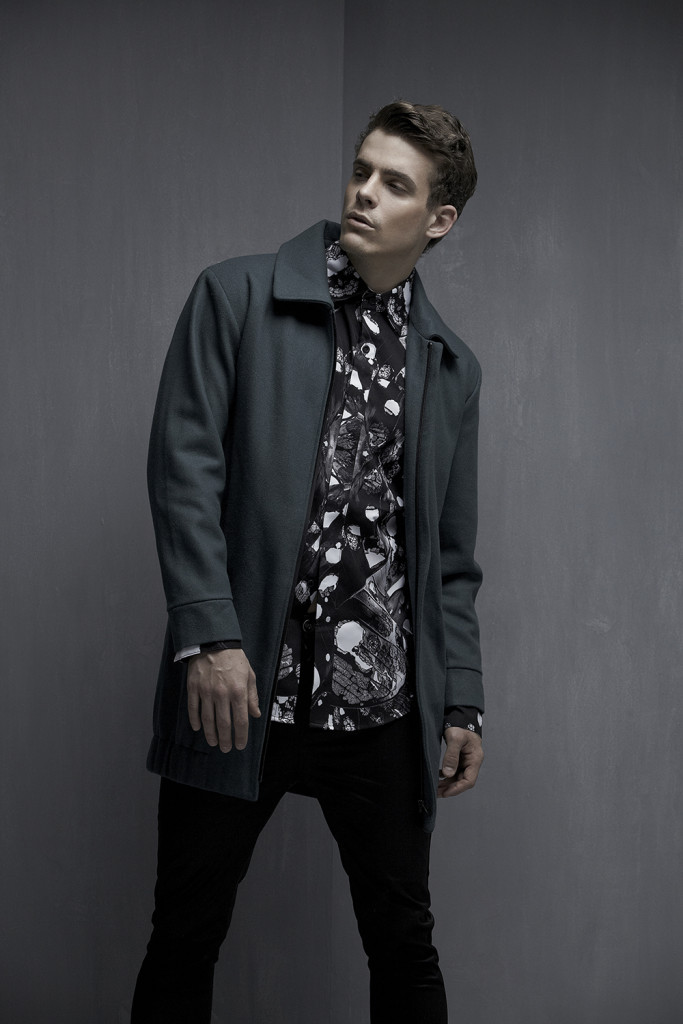 Model standing in front of a grey wall in a grey jacket, patterned shirt and black pants.