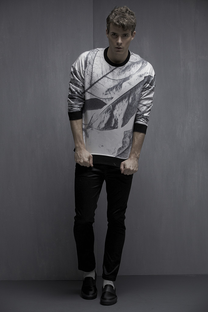 Male model standing in front of a grey wall in black pants and a digital print long sleeved T.