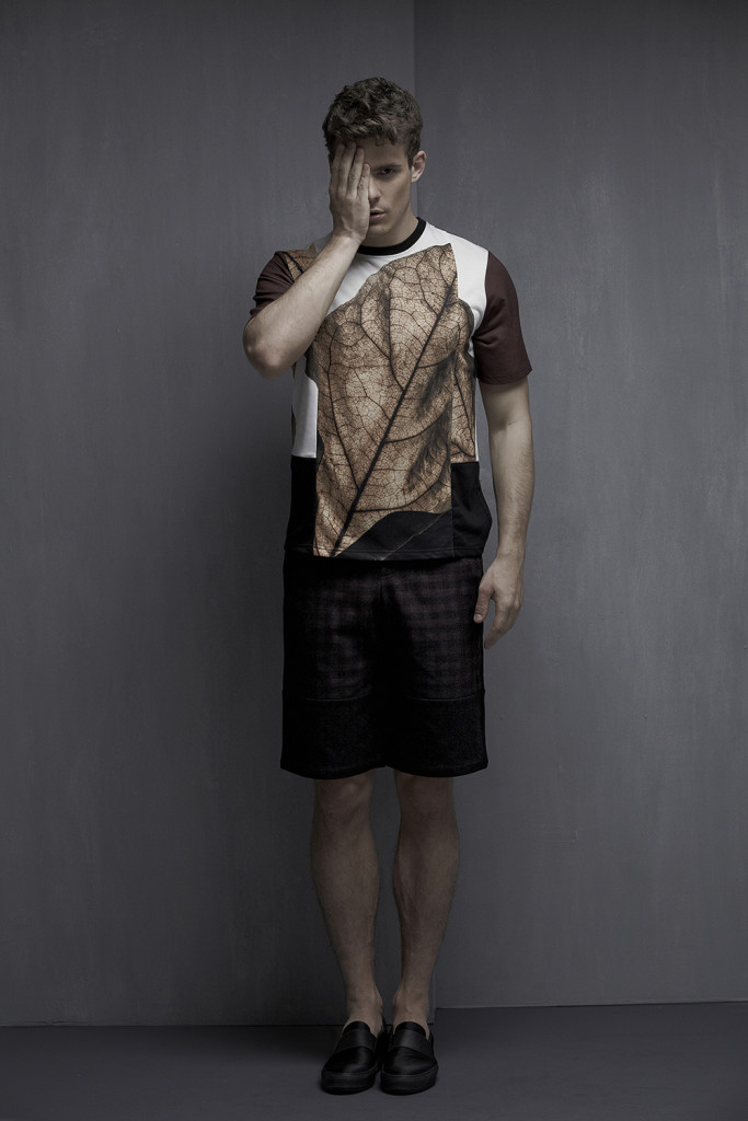 Male model standing in front of a grey wall in black shorts and a patterned T with short sleeves and a rust leaf motif on the front.