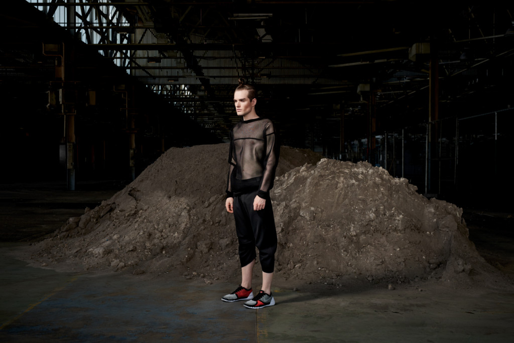 Model standing in an urban setting under a bridge dressed in the sports-luxe wear and technical fabric inspired by pop and internet culture, and elemental street styling.