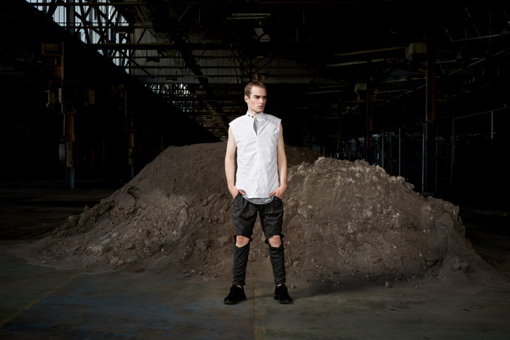 Model standing in a area of earth moving soil in casual sports luxe attire.