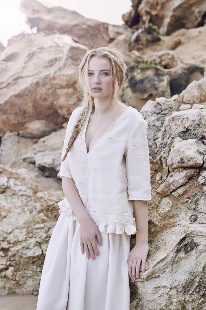 Model wearing Lois Hazel in a beach setting with honeycomb caves behind her in a loose fitting v neck top with matching skirt.