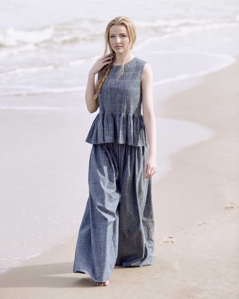 Model standing on Sorrento Beach in blue wide leg pants with a blue top with peplum flare design with bare feet with the headland behind her.