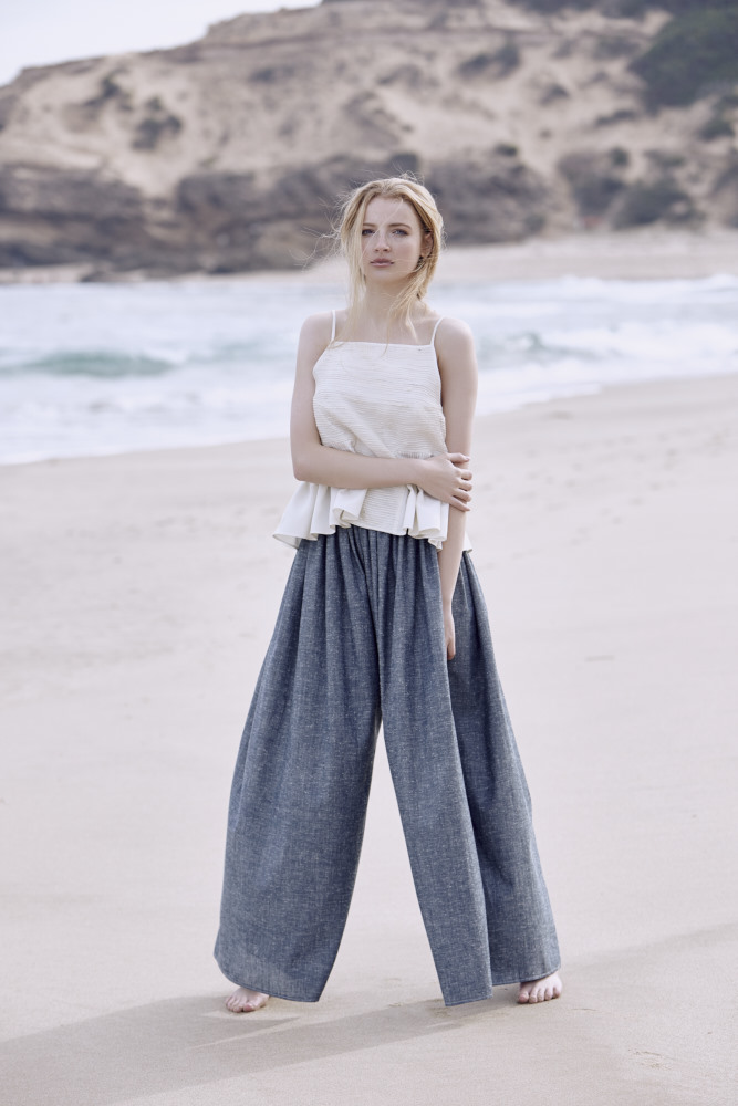 Model standing on Sorrento Beach in blue wide leg pants with a white top with shoe string straps with bare feet with the headland behind her.