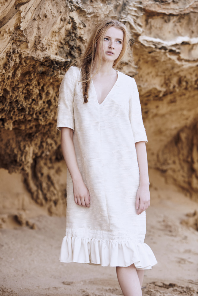 Model wearing Lois Hazel in a beach setting with honeycomb caves behind her in a loose fitting v neck dress with frill hemline.