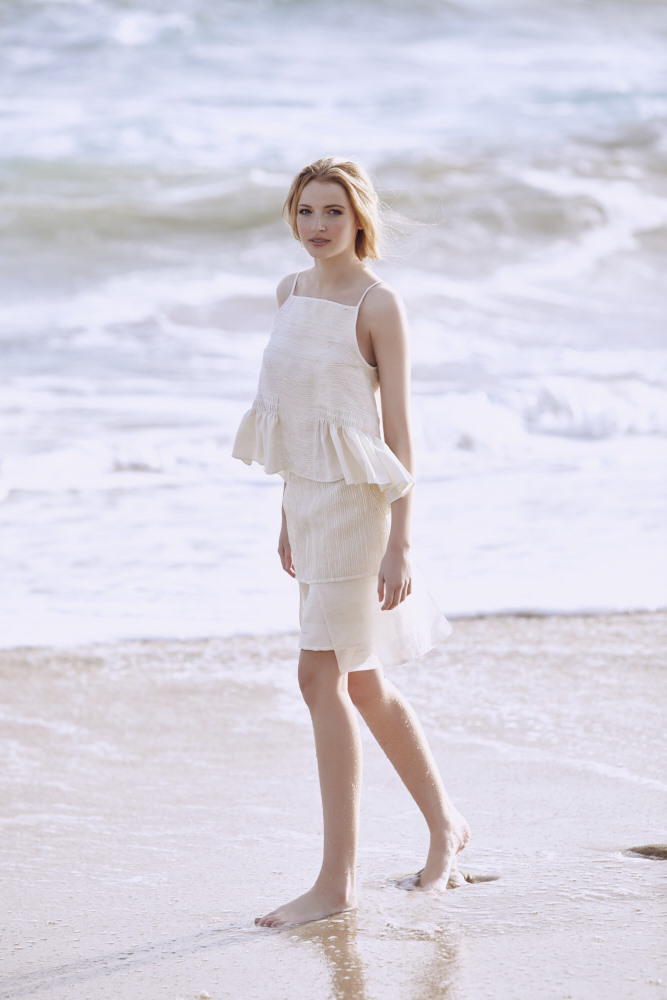 Model at Sorrento beach standing barefoot on the sand wearing a Lois Hazel cream skirt and cream top with shoe string straps.