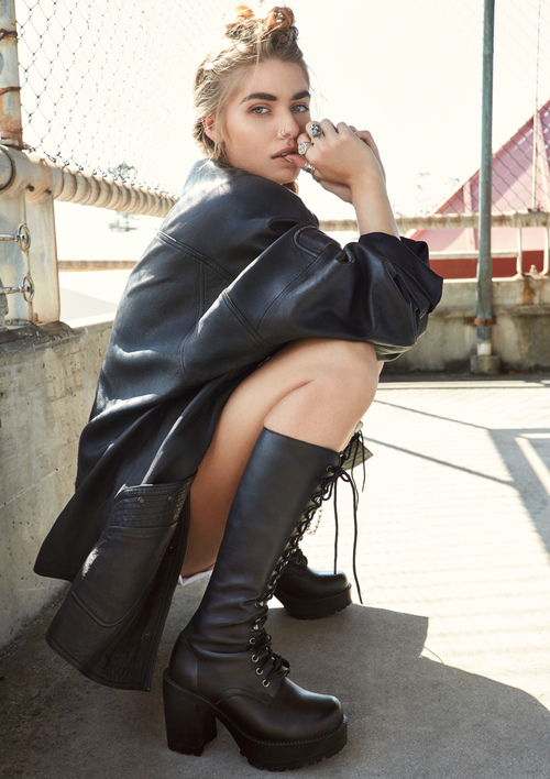 Girl squatting in black knee high high heeled boots, shorts and leather jacket photographed on location in an urban setting in front of a concrete and steel railing fence.