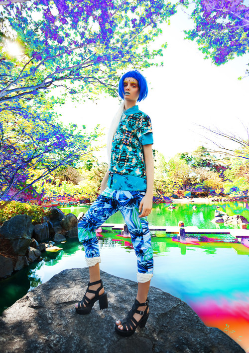 Model with blue hair standing in colourful skirt and top with high heeled black strappy shoes for a campaign shoot.