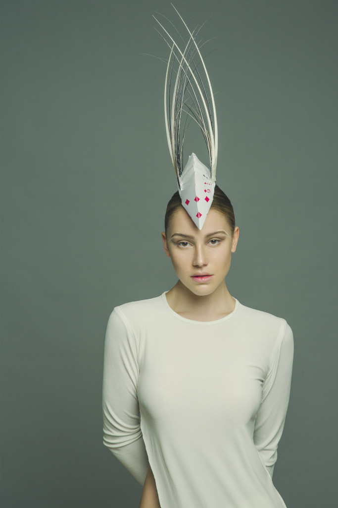 Model standing in a studio wearing the millinery work of Andrew Cannon, a Canberra milliner know as Andrew James Millinery.
