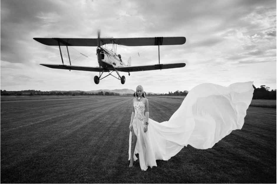 Model standing on an airfield in a beautiful white flowing dress, completely lace up open boots and vintage beaded head gear with an old fashioned aircraft taking off the background behind her. Very hollywood setting and incredibly creative the a real feel of movement to the picture.